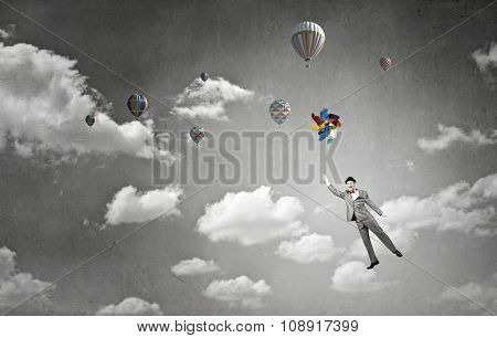 Young happy businessman in hat flying in sky on colorful windmill