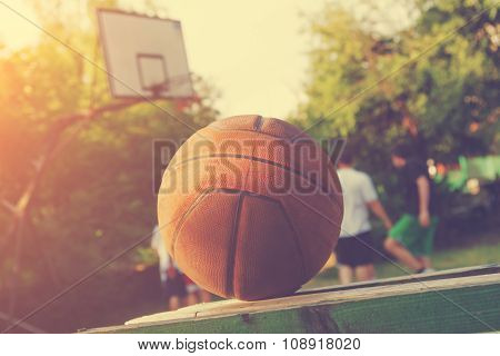 Basketball ball detail with de-focused players.