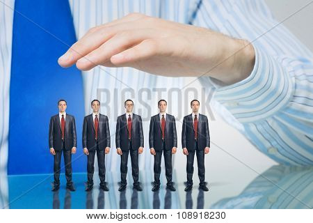 Male hand protecting business people of different size