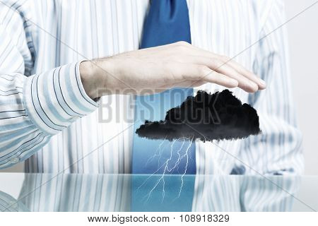 Hand of businessman protecting black raining cloud