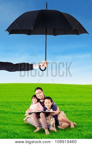 Dad Children Sitting Under Umbrella