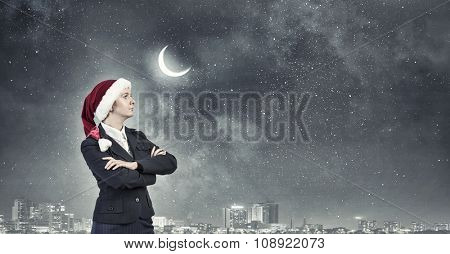 Woman in suit and Santa hat with arms crossed on chest