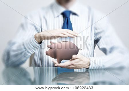 Hands of businessman protecting piggy bank with palms