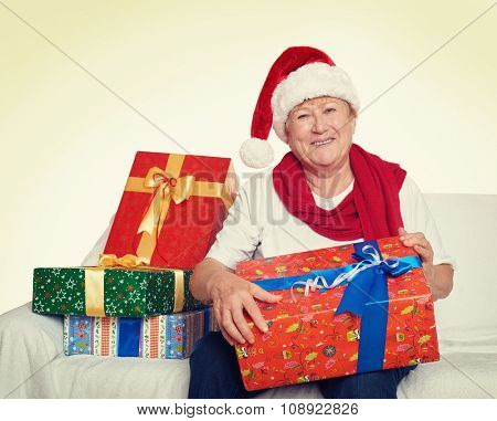 elderly woman with christmas box gift - happy holiday concept