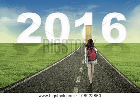 Female Student Walking Toward Numbers 2016