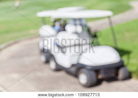 Blurred Photo Of Golf Cart Parks In Golf Course Waiting For Golfers.