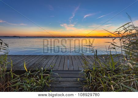 Blue And Orange Sunset Over Boardwalk On The Shore Of A Lake