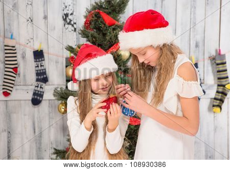 Teenage girls decorating New Year tree at home