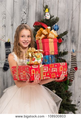 Teenage girl holding Christmas presents in front of New Year tree