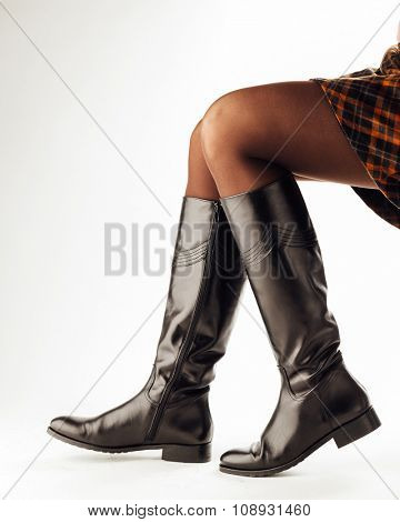 woman legs wearing black leather high boots, white background