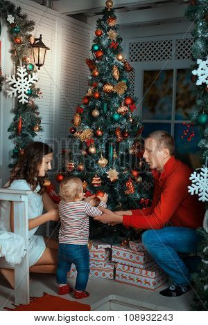 Parents And Child Near A Christmas Tree