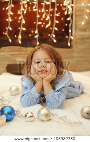 Little girl at home with Christmas balls