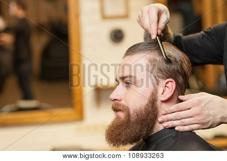 Cheerful male barber is serving his client