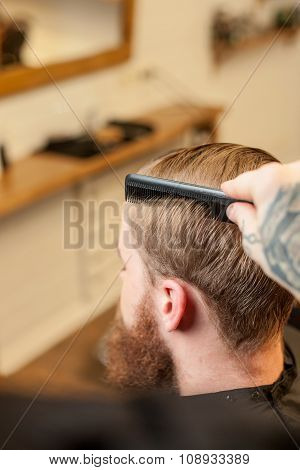 Professional male hairdresser is working with comb