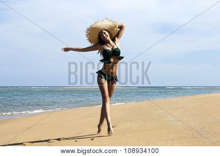 Woman in hat on beach. Beautiful smiling girl wearing green bikini poses walking near sea. Fashion l