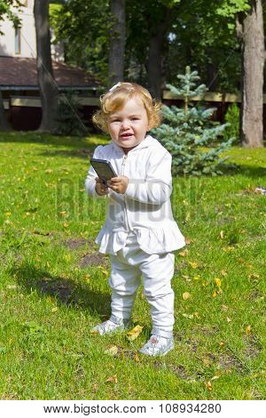 Cute Infant With Cellular In Summer