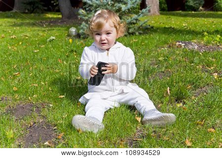 Cute Infant With Cellular Sitting On Green Grass