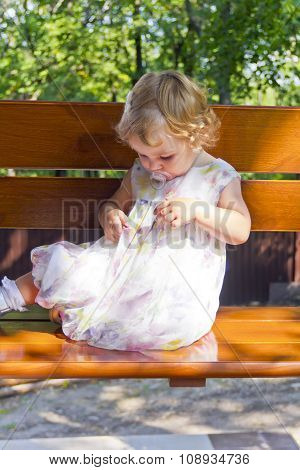Cute Infant Sitting On Bench