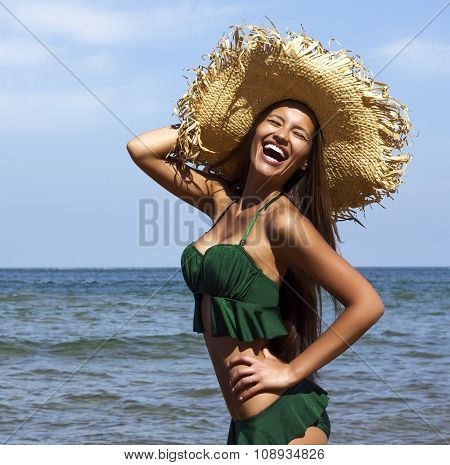 Woman in hat on beach. Beautiful smiling girl wearing green bikini poses near sea. Fashion look.Trop