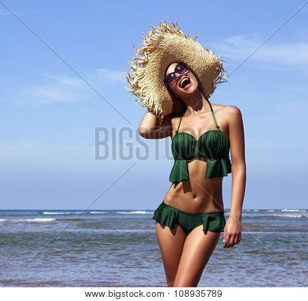 Woman in hat with sunglasses on beach. Beautiful smiling girl wearing green bikini poses near sea. F