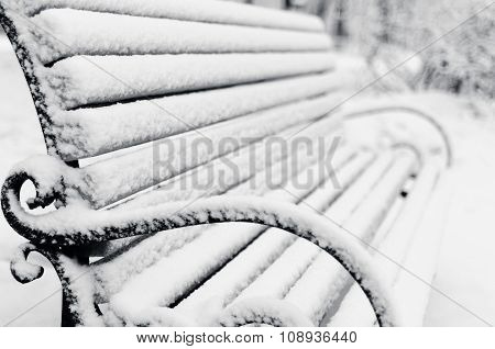 single bench close-up covered with snow in Winter Park
