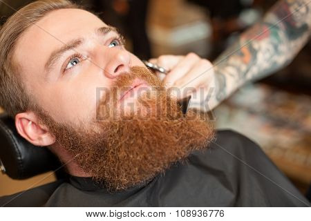 Cheerful bearded hipster is attending hair salon