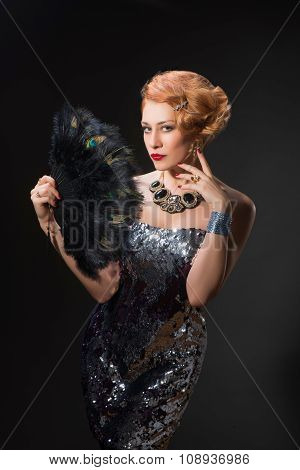 woman in vintage style dress holding fan of peacock feathers