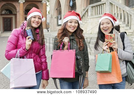 christmas shopping 3 happy smiling girls with santa hats and shopping bags