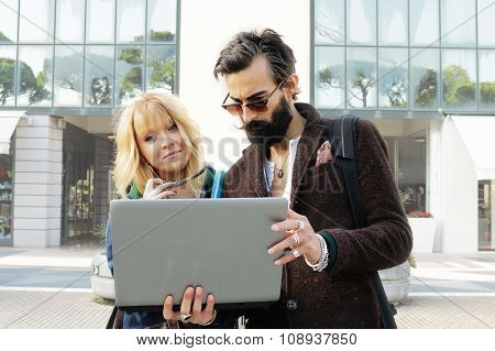 couple of young office mates with laptop computer outside office