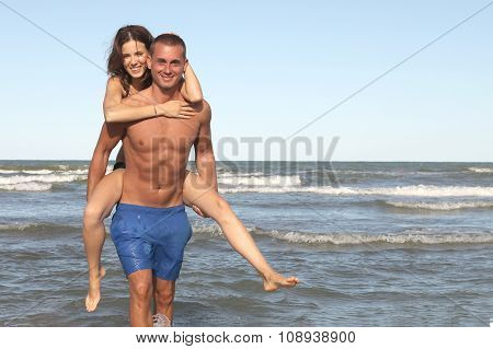 young couple play in sea water, girl in bikini on piggyback ride with the guy on beach vacation
