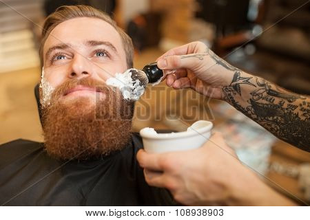 Cheerful bearded hipster is visiting his hairdresser