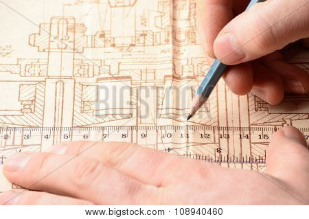 Man's Hand Holding A Pencil On The Drawing
