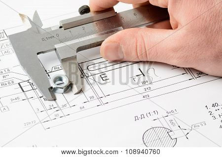 Man's Hand Measuring A Nut Over The Drawing