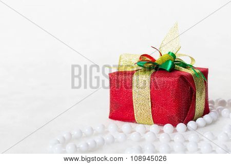 Red Christmas gift box with shiny silver ribbon and beads