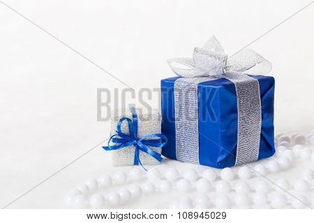 Blue Christmas gift box with shiny silver ribbon and beads