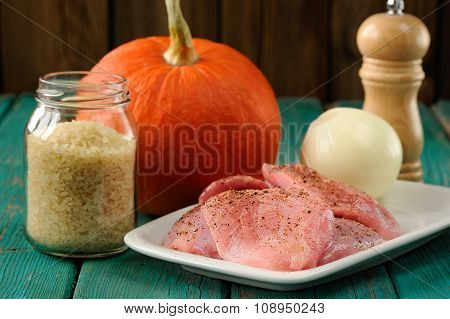 Raw Meat, Whole Pumpkin, Onion And Rice With Pepper Mill