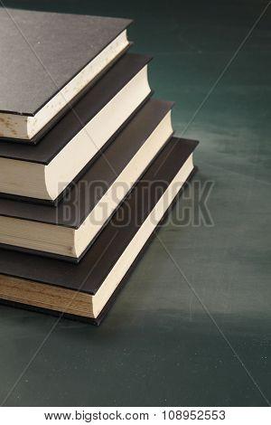 stack of books on the blackboard