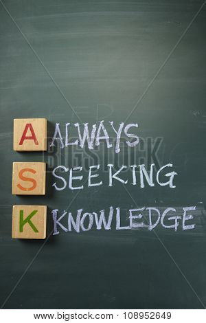 Hand writing ASK - Always Seek Knowledge with white chalk on blackboard.