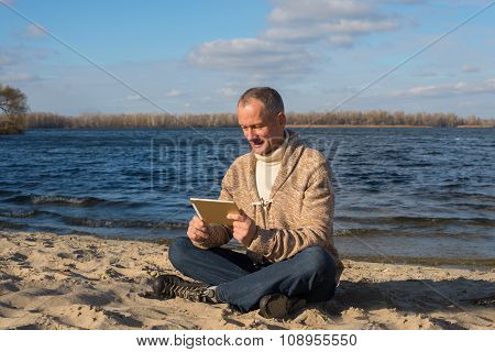 Smiling Man, Wearing Casually, Using His Tablet While Relaxing At The Coast, And Enjoying Life In Ma