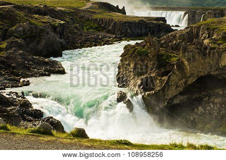 Glacial river with Godafoss waterfall in background, Iceland