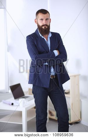 Handsome young businessman standing with arms crossed in office