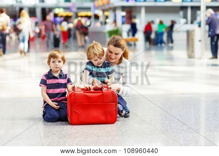 Mother and two little sibling boys at the airport