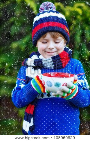 Little kid boy holding big cup with chocolate drink in winter