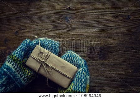 Hand in knitted mittens holding present, rustic wood background