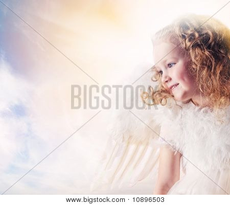 Little angel girl against beautiful sunny sky