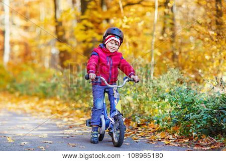 Little kid boy with bicycle in autumn forest
