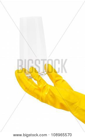 Close up of female hand in yellow protective rubber glove holding clean transparent drinking glass