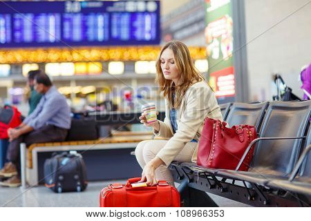woman at international airport waiting for flight at terminal