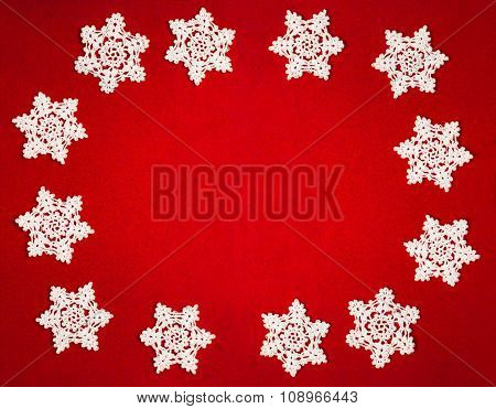 Circle Of Twelve White Crochet Snowflakes On Red Felt Background