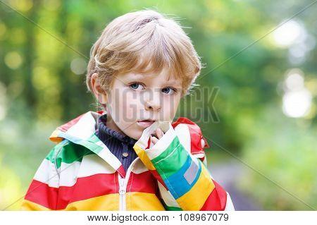 Portrait of blond little preschool  boy in colorful waterproof r
